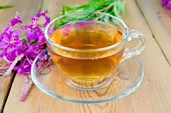 Herbal tea in a glass cup, fresh flowers fireweed on a wooden boards background