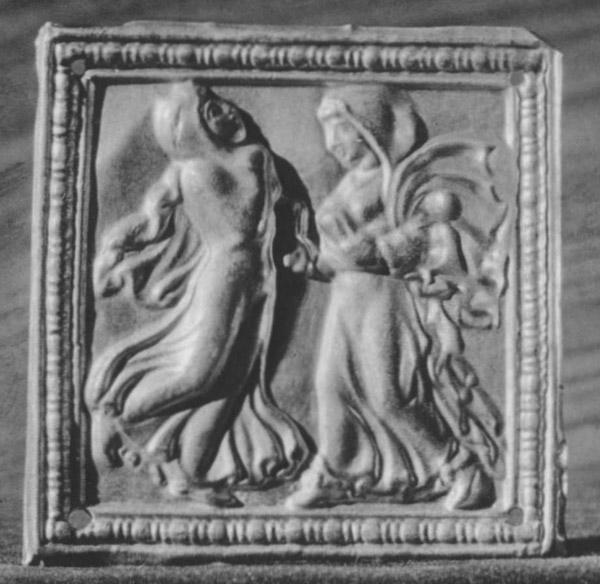 Четырехугольная золотая бляшка с рельефным изображением двух танцующих женских фигур в рамке.